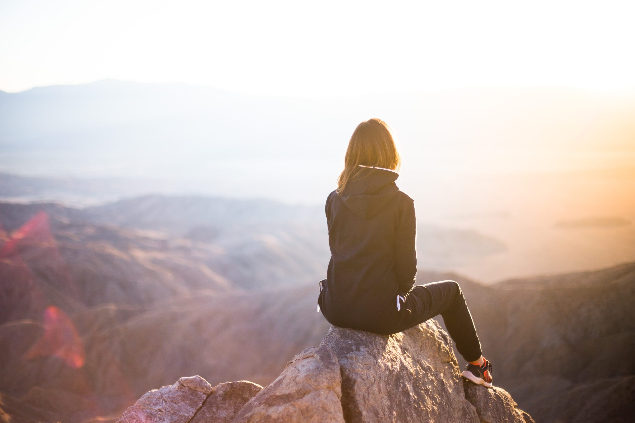 A woman's back is visible as she sits on a rock looking at the mountain range with sun falling