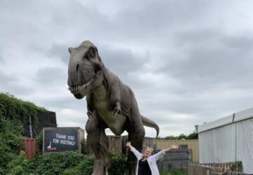 The writer standing in front of an animatronic dinosaur.