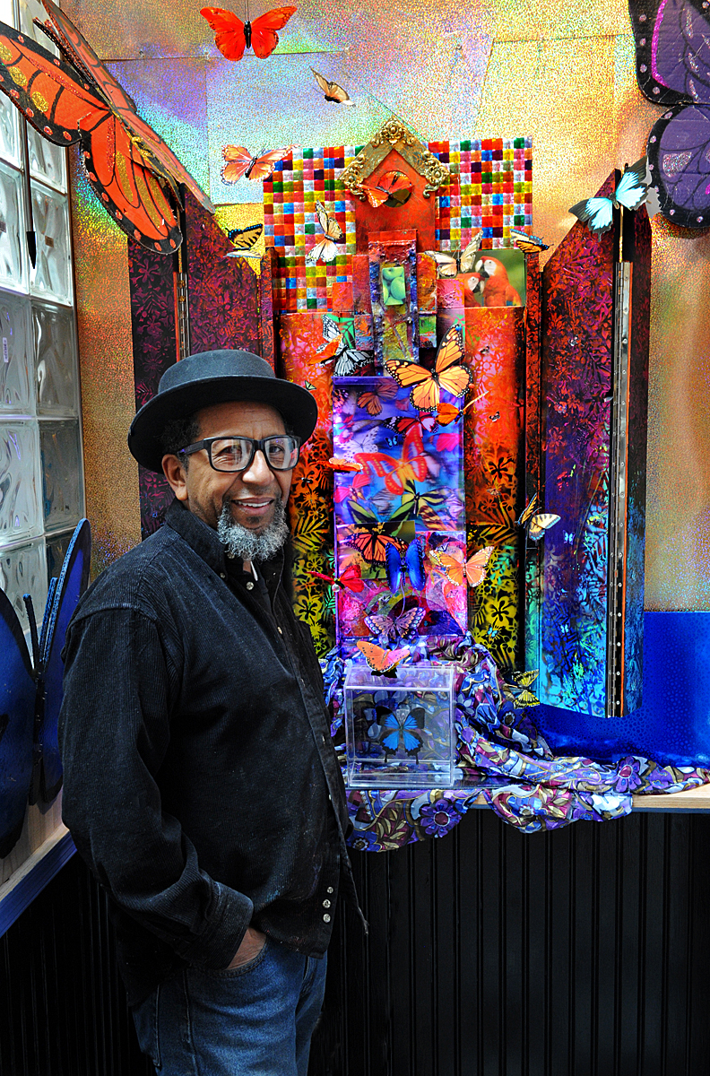 James Dupree, a Black man, stands in front of a colorful art piece he created. He has a grey beard and is wearing jeans, a small black hat, and a button down black shirt. He is dressed casually and also wears glasses.