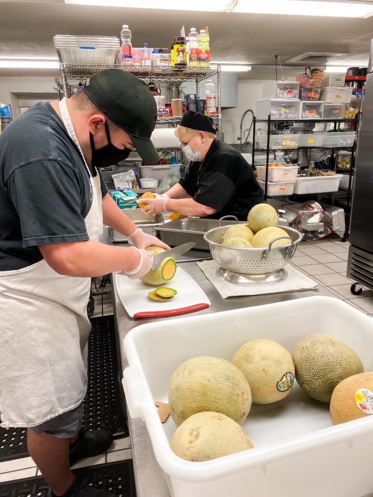 Liz and a volunteer cutting cantaloupes