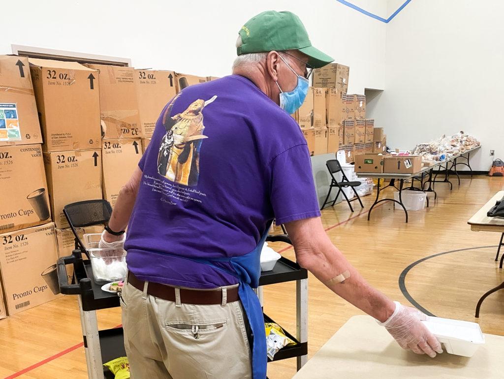A volunteer serving lunch