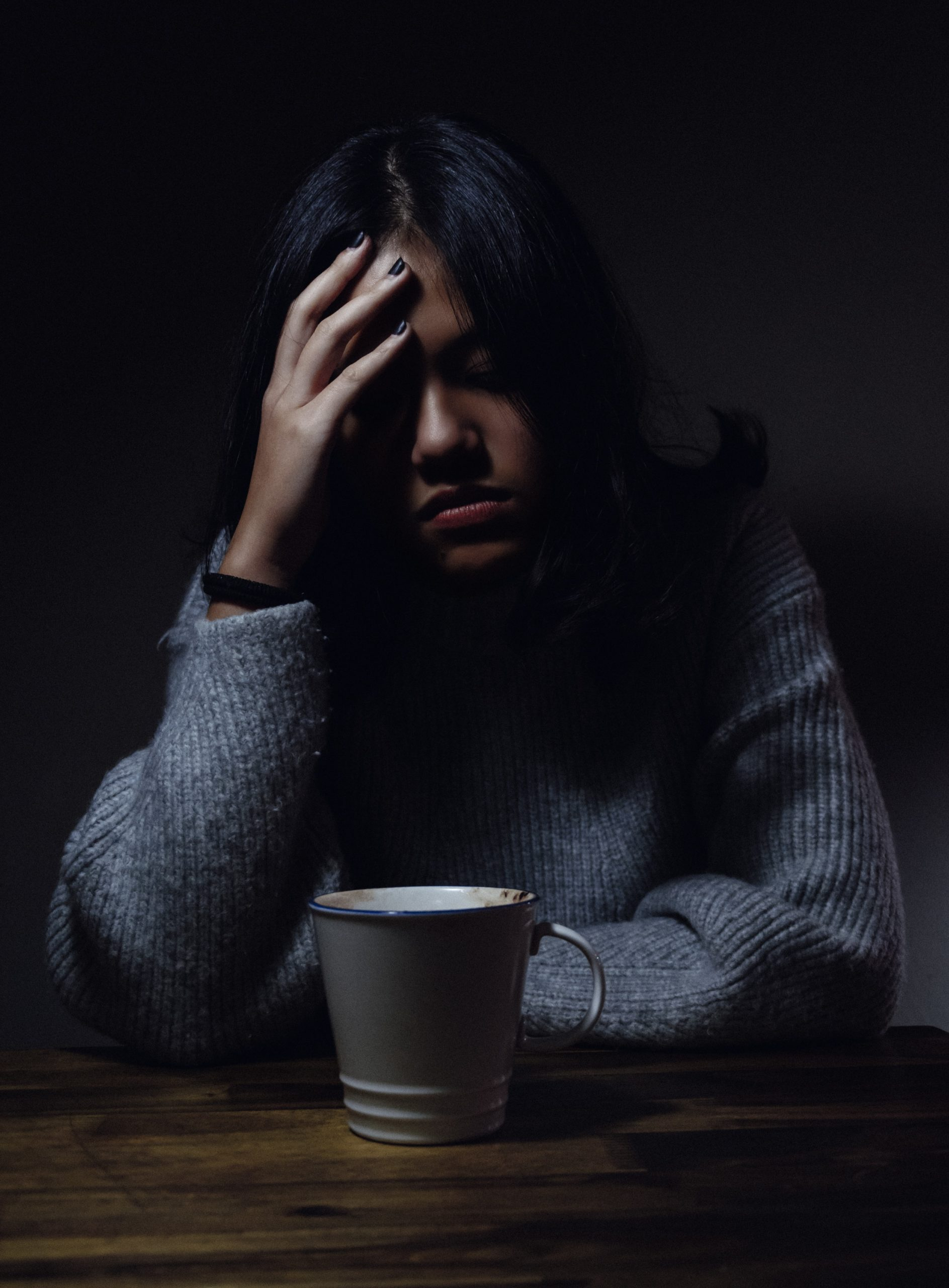 Woman in a gray sweater sitting in a dark room in a depressive state.