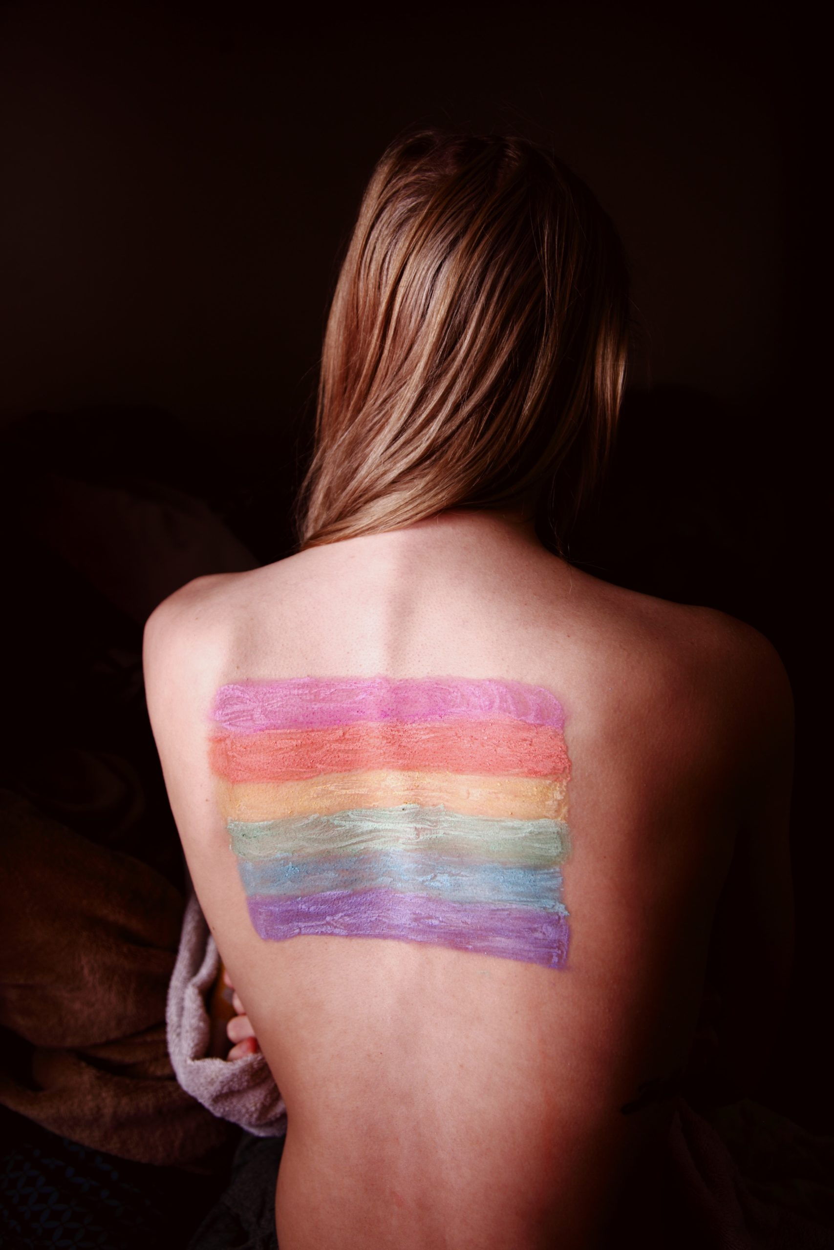 Girl with LGBTQ+ flag on her back
