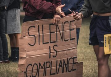 "Person holding a cardboard sign that says ""Silence is Compliance"" in all caps with black marker."
